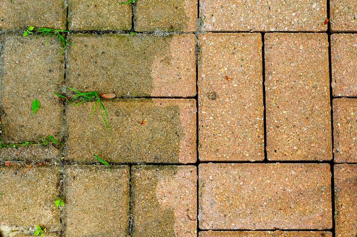 Groene aanslag mossen en gras vervuilen de terrasklinkers