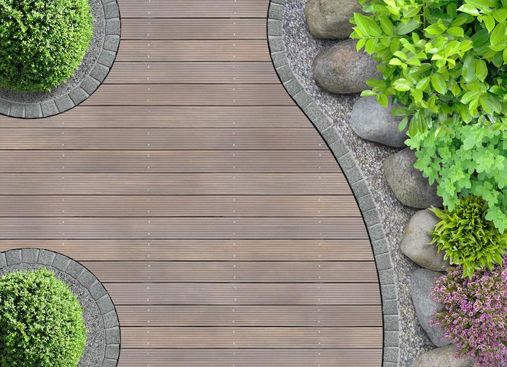 Kronkelend houten tuinpad met plantenborder en boordsteen in klinkers