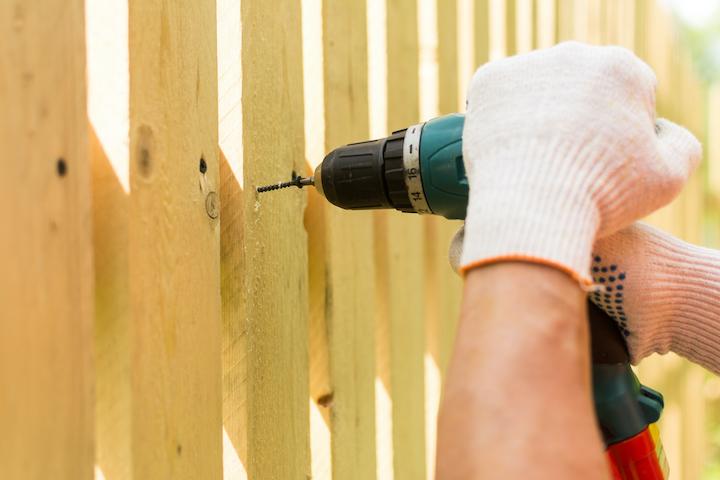 Plaatsing van een decoratieve houten afsluiting door tuinaannemer