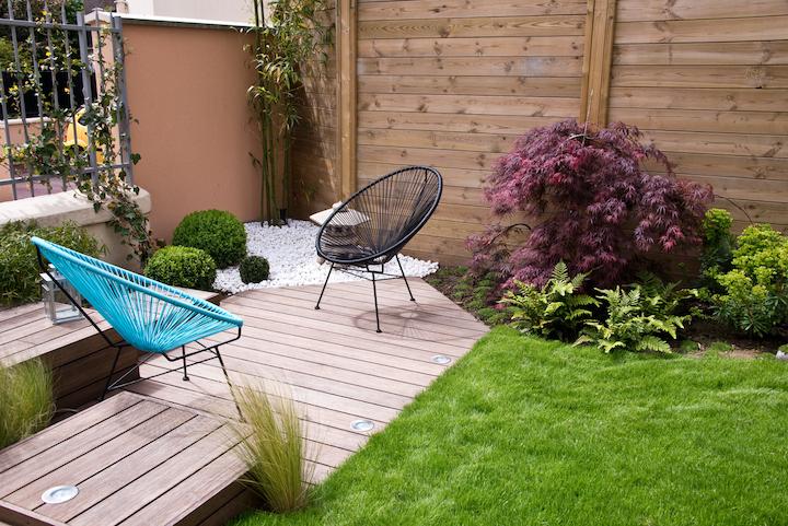 Kleine stadstuin met houten terras en plantenborder