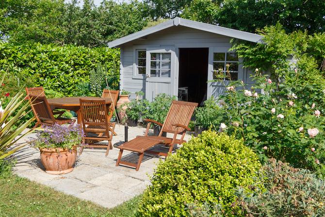 Tuinhuis nabij zithoek in de tuin met houten tuinmeubelen